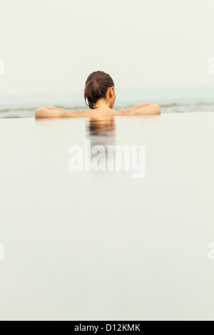 India, Kerala, Young woman relaxing in pool - Stock Photo