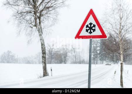 Road sign beside wintry road in Bavaria/Germany - Stock Photo