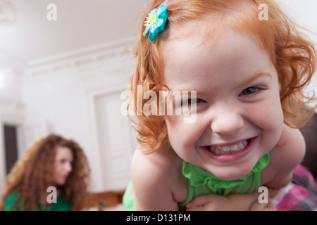 Germany, Berlin, Girl having fun at home, woman in background - Stock Photo