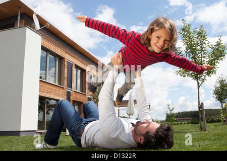 Germany, Bavaria, Nuremberg, Father balancing his son - Stock Photo