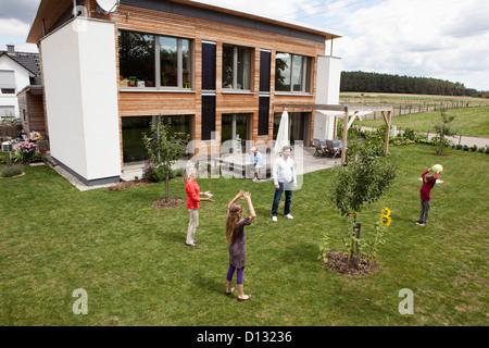 Germany, Bavaria, Nuremberg, Family playing in garden - Stock Photo