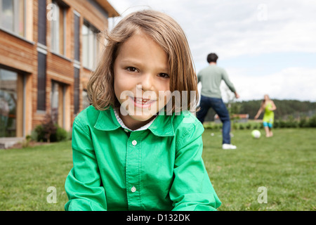 Germany, Bavaria, Nuremberg, Boy smiling, portrait, father and daughter playing in background - Stock Photo