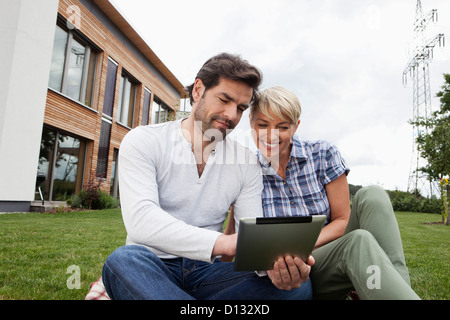 Germany, Bavaria, Nuremberg, Mature couple using digital tablet in garden - Stock Photo