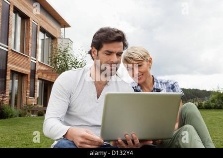 Germany, Bavaria, Nuremberg, Mature couple using laptop in garden - Stock Photo