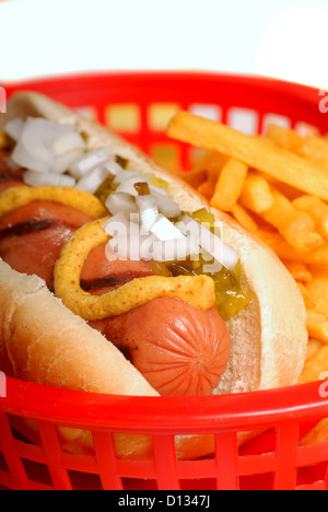 Freshly grilled hot dog in a basket with french fries - Stock Photo