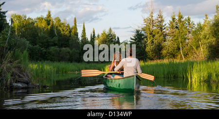 Teenage Girls Paddling A Canoe In A Lake; Lake Of The Woods Ontario Canada - Stock Photo