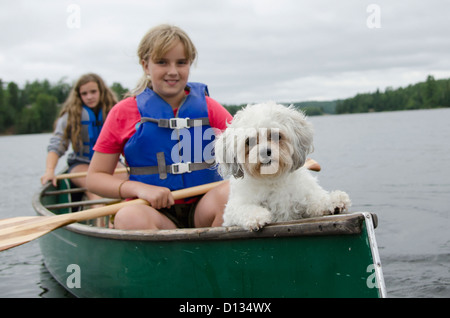 Two Girls In A Canoe With Their Pet Dog; Lake Of The Woods Ontario Canada - Stock Photo