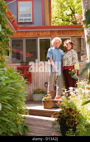 Senior Couple Standing In Their Home Garden; Winnipeg Manitoba Canada - Stock Photo