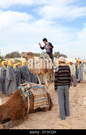 The guide shows visitors how to get on and ride of the camel. Douz, Tunisia, Africa - Stock Photo