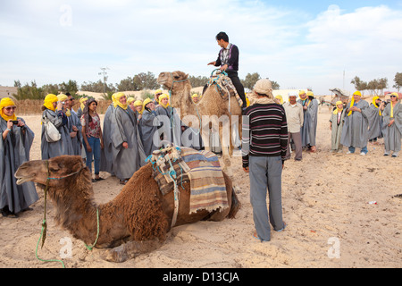 The guide shows visitors how to ride on the camel. Douz, Tunisia, Africa - Stock Photo