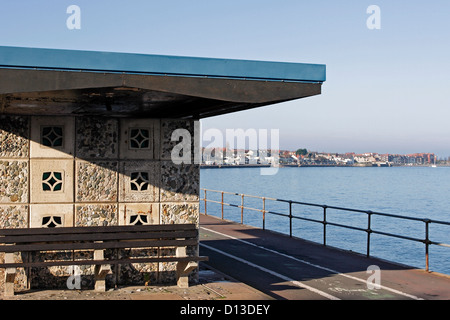 A seaside seating shelter on the promenade in Colwyn Bay, North Wales with Rhos on Sea visible in the distance. - Stock Photo