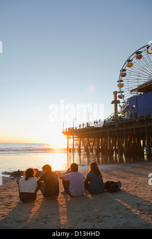 Four Friends Sitting On The Beach Next To Santa Monica Pier; Los Angeles California Usa - Stock Photo