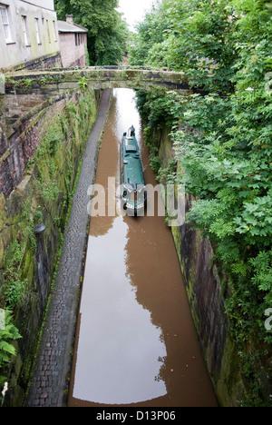 Green Narrowboat Chalico navigating the Shropshire Union Canal - Stock Photo