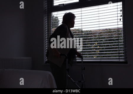 Senior woman alone with a walking frame looking out of a window blind. Rear or side view, silhouette. - Stock Photo