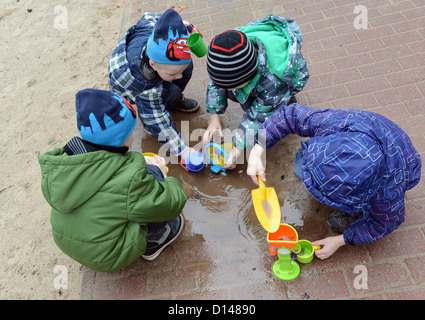 A group of children play in a puddle at a childrens' nursery in Berlin, Germany, 30 November 2012. Photo: Jens Kalaene - Stock Photo