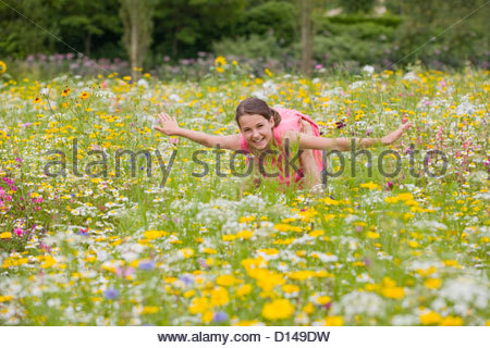 Father holding flying among wildflowers in sunny meadow - Stock Photo