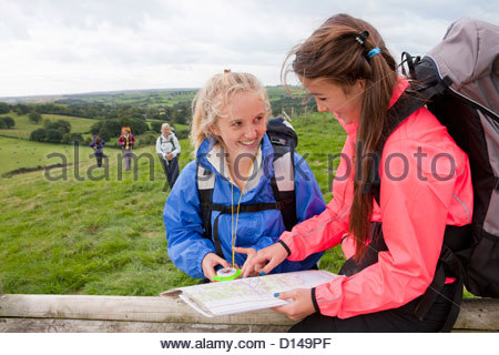 Smiling girls with backpacks looking down at compass and map - Stock Photo