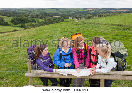 Girls with backpacks looking down at compass and map against fence in field - Stock Photo