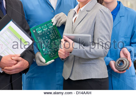 Close up of business people and engineers with printed circuit board and machine part in manufacturing plant - Stock Photo