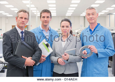 Portrait of confident business people and engineers in machine part manufacturing plant - Stock Photo