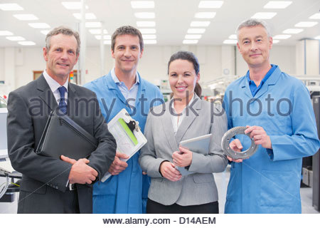 Portrait of confident business people and engineers in machine part manufacturing plant, - Stock Photo
