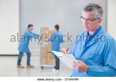 Worker with clipboard in warehouse - Stock Photo