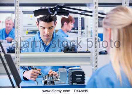 Technicians assembling circuit boards in manufacturing plant - Stock Photo