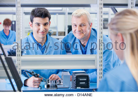 Portrait of smiling supervisor and technician assembling circuit board in manufacturing plant - Stock Photo