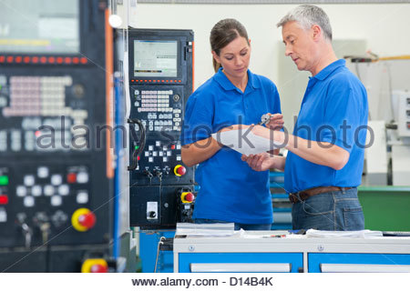 Engineers discussing paperwork in manufacturing plant - Stock Photo