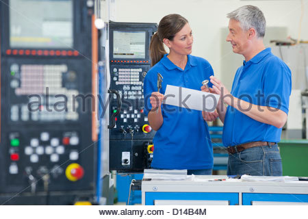 Engineers with tools discussing paperwork in manufacturing plant - Stock Photo