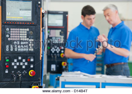 Engineers discussing machine parts in manufacturing plant - Stock Photo