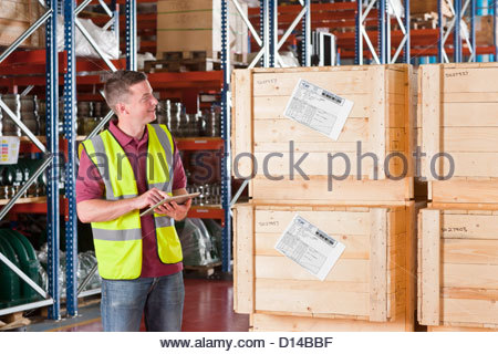 Smiling worker with digital tablet checking crates in warehouse - Stock Photo