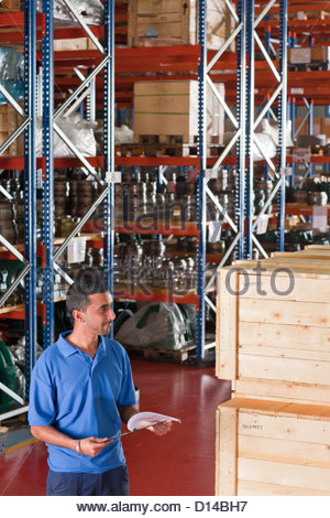 Smiling worker holding clipboard and checking crates in warehouse - Stock Photo