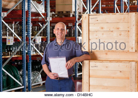 Portrait of smiling worker holding paperwork and leaning on crates in warehouse - Stock Photo