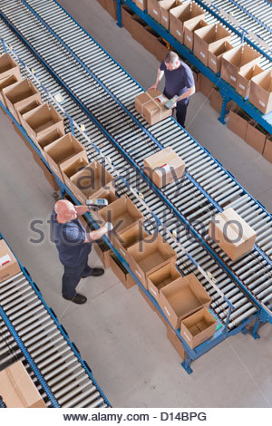 Workers packing boxes on conveyor belts in distribution warehouse - Stock Photo