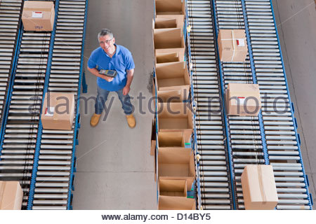 Portrait of smiling worker holding bar code reader among boxes on conveyor belts in distribution warehouse - Stock Photo