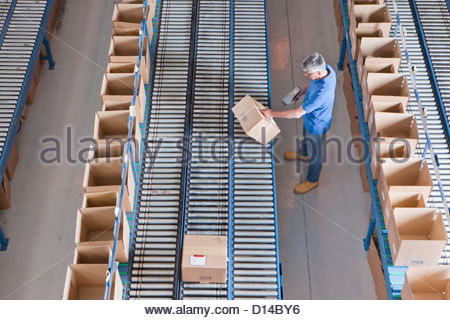 Worker with bar code reader scanning box on conveyor belt in distribution warehouse - Stock Photo