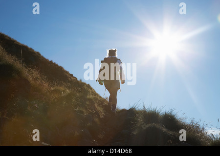 Woman hiking on rural hillside - Stock Photo