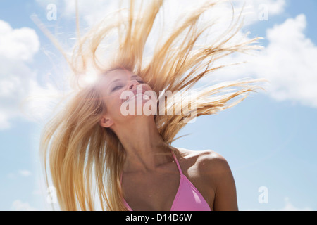 Smiling woman tossing her hair - Stock Photo