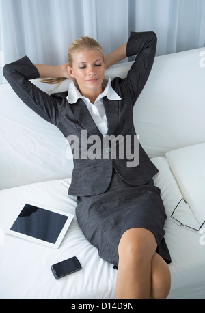 Businesswoman relaxing on sofa - Stock Photo