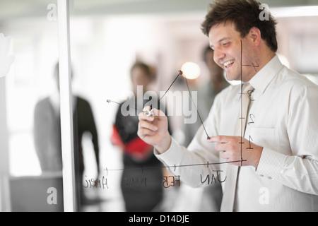 Businessman drawing graph on window - Stock Photo