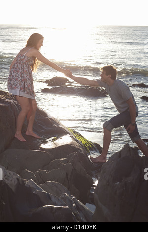 Couple climbing rocks on beach - Stock Photo