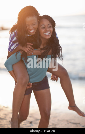 Woman carrying friend on beach - Stock Photo