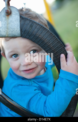 Toddler boy sitting in swing outdoors - Stock Photo