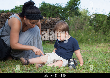 Mother putting bandage on boys knee - Stock Photo