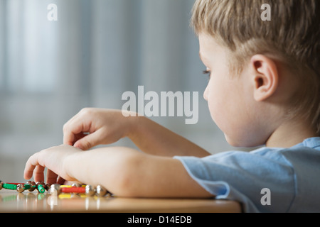 young boy playing with shape game - Stock Photo