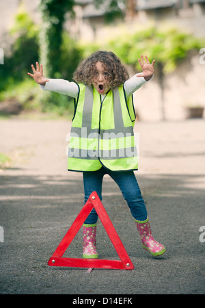 Girl playing traffic worker on rural road - Stock Photo