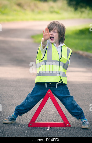 Boy playing traffic worker on rural road - Stock Photo