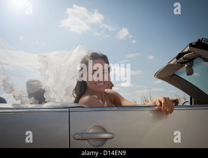 Newlywed couple driving in convertible - Stock Photo