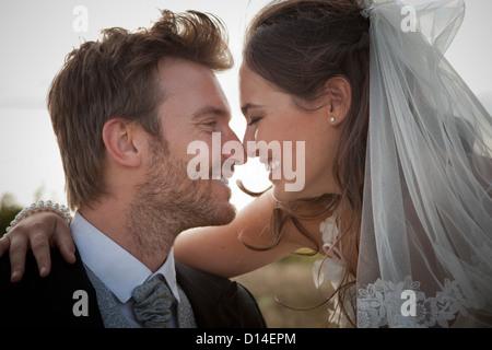 Newlywed couple touching noses - Stock Photo